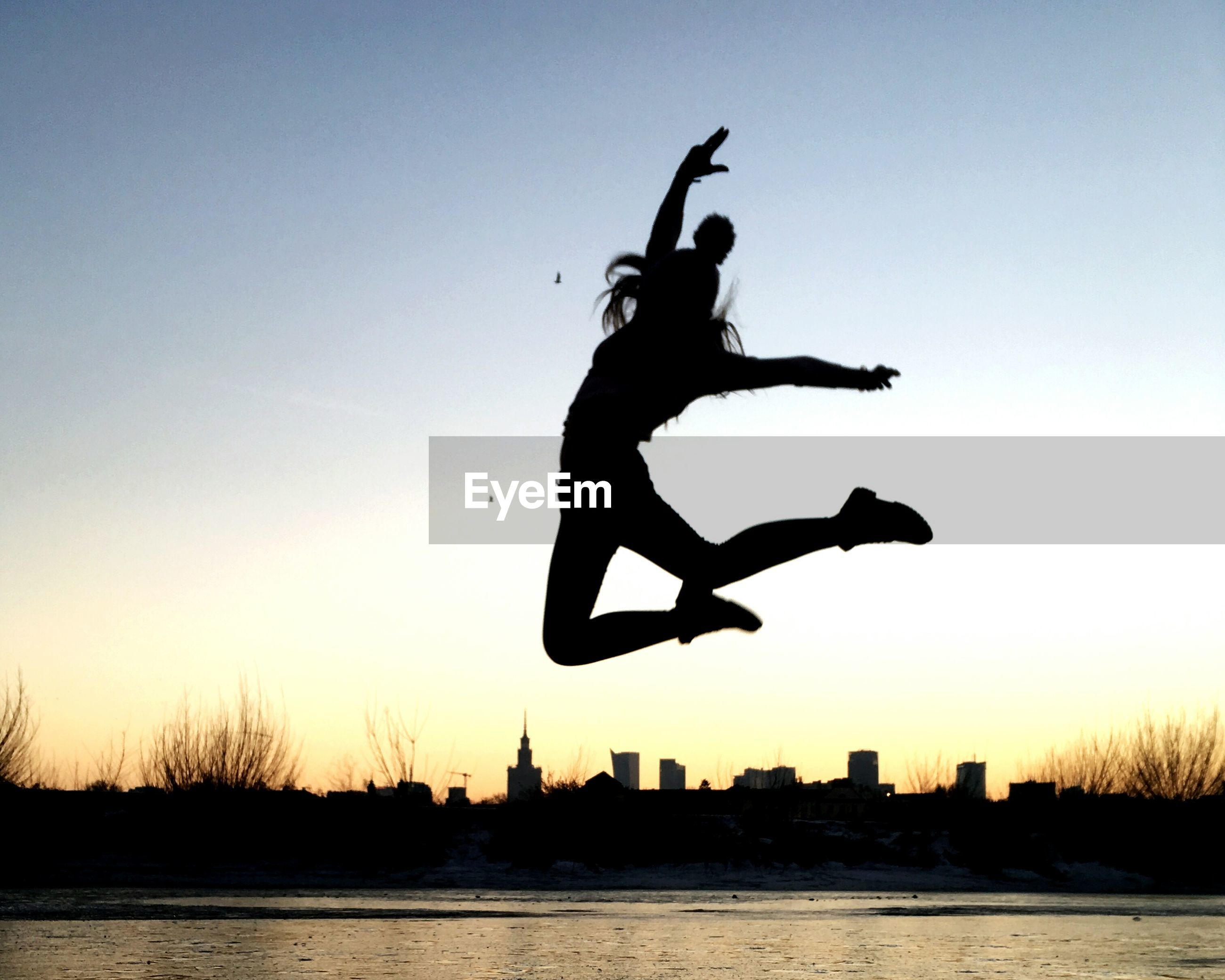 Silhouette of girl jumping at sunset