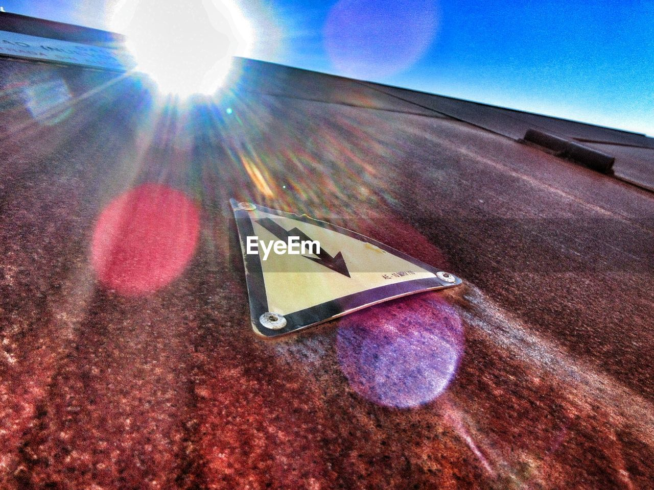 lens flare, sunbeam, sunlight, no people, sun, day, low angle view, outdoors, sky, road sign, close-up