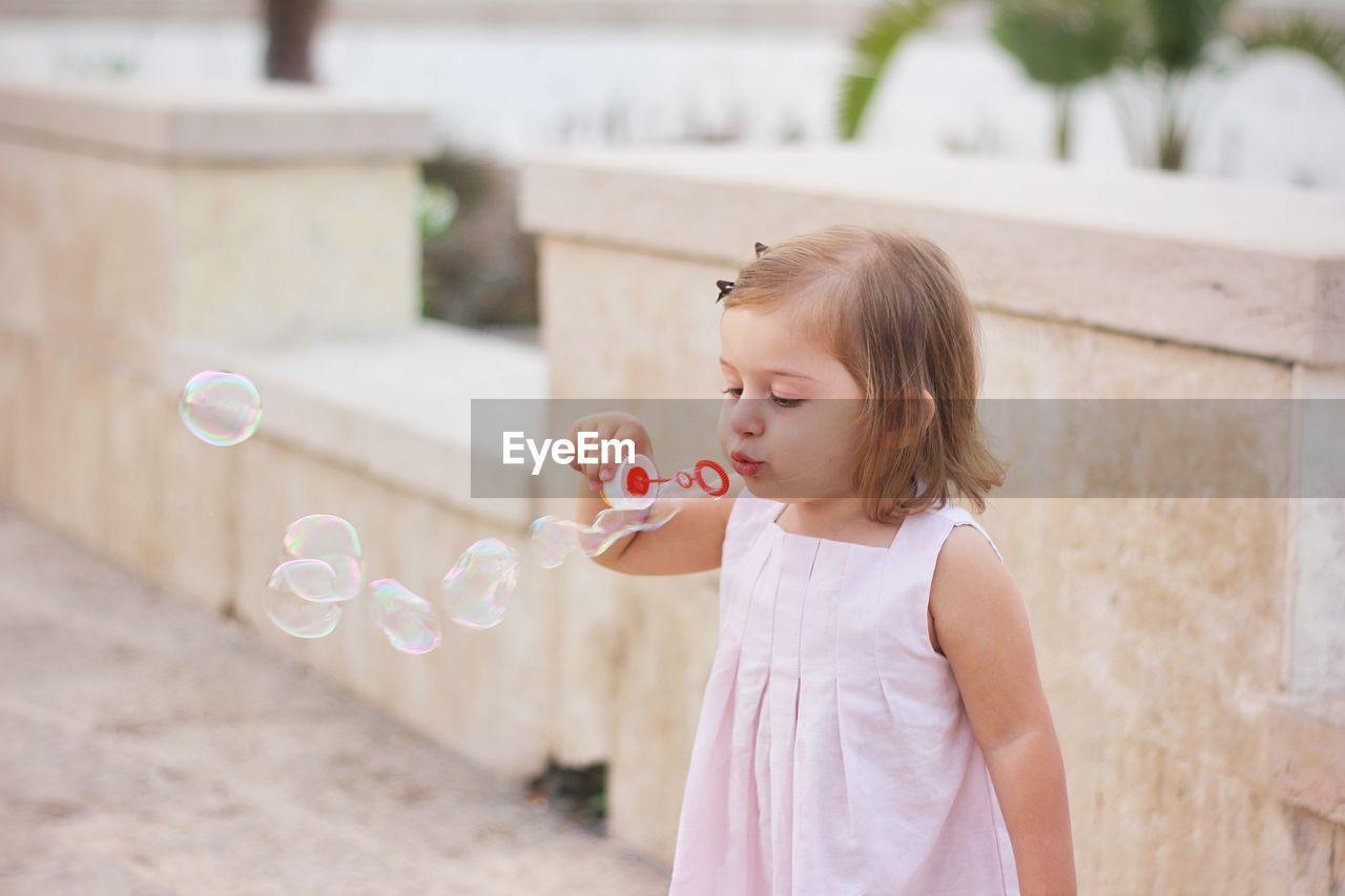 Girl Blowing Bubble From Wand