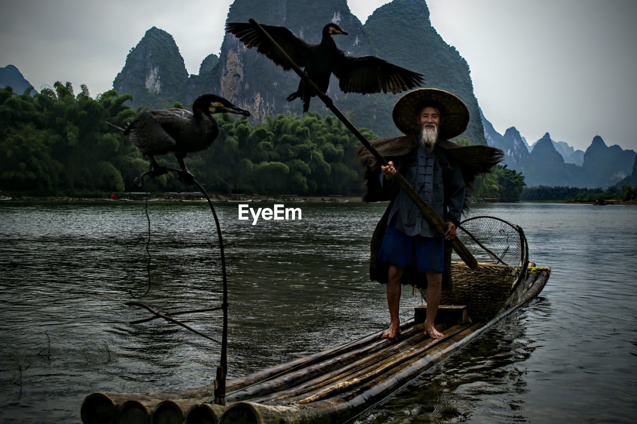 Chinese fisherman on traditional wooden raft