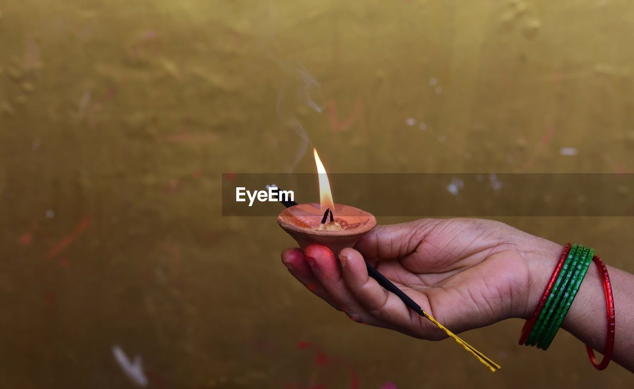 Cropped Hand Of Woman Holding Lit Diya And Incense