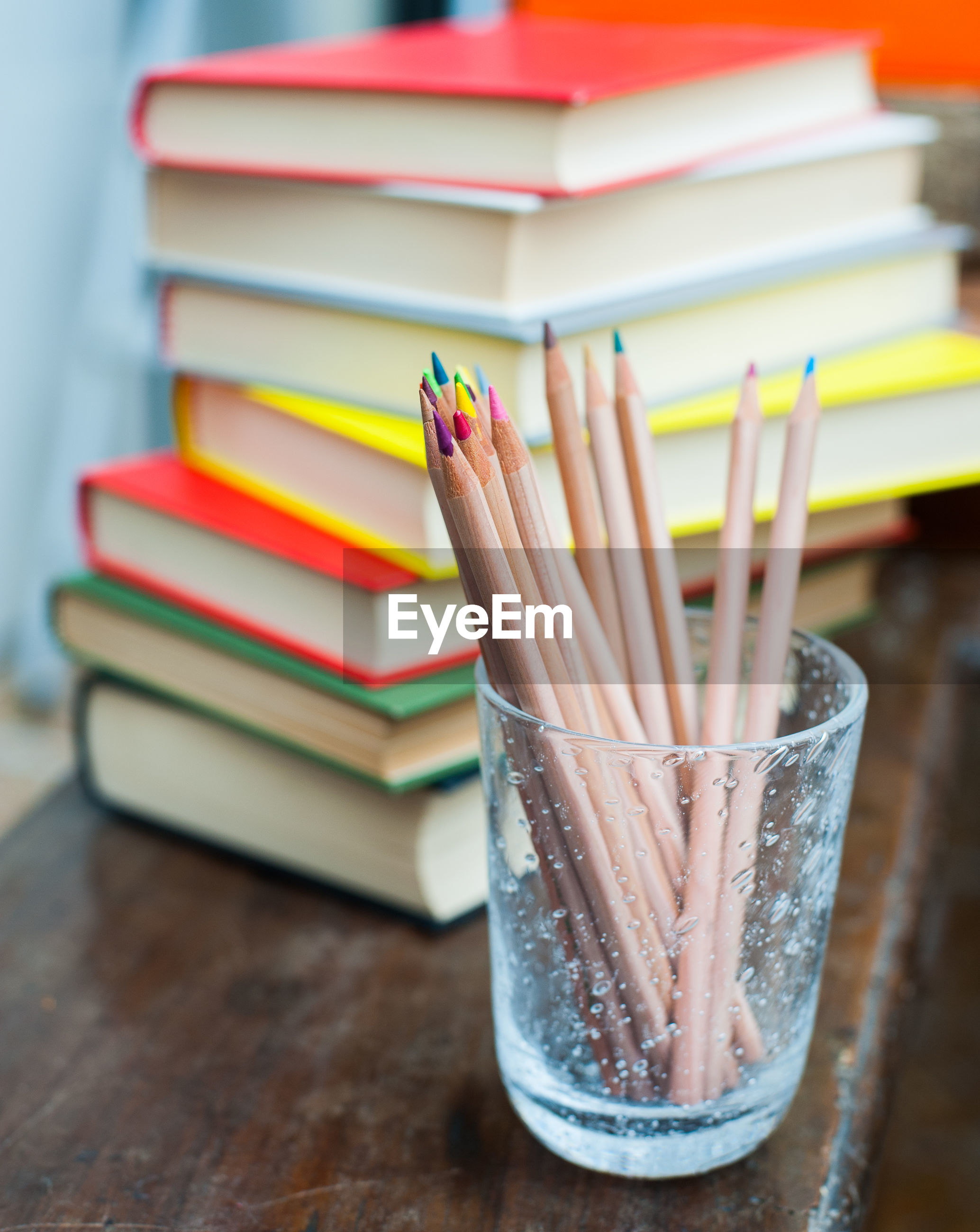 Close-up of colored pencils in glass by stacked books on table