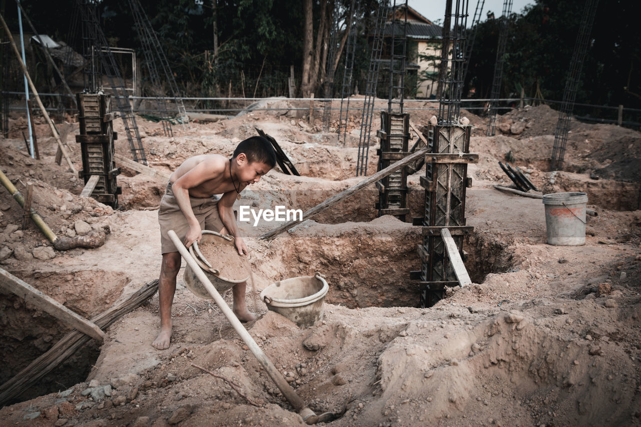 SIDE VIEW OF A MAN WORKING IN FARM