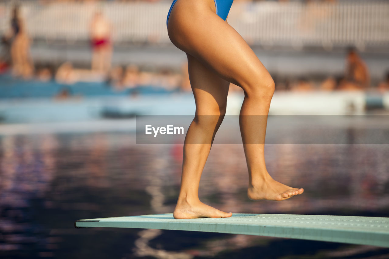 Low Section Of Woman Jumping Diving Board
