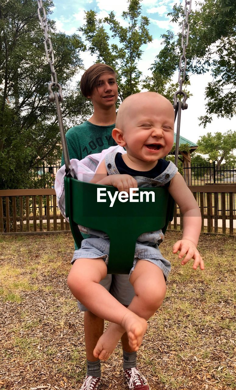 Teenage boy standing by cute brother swinging in playground