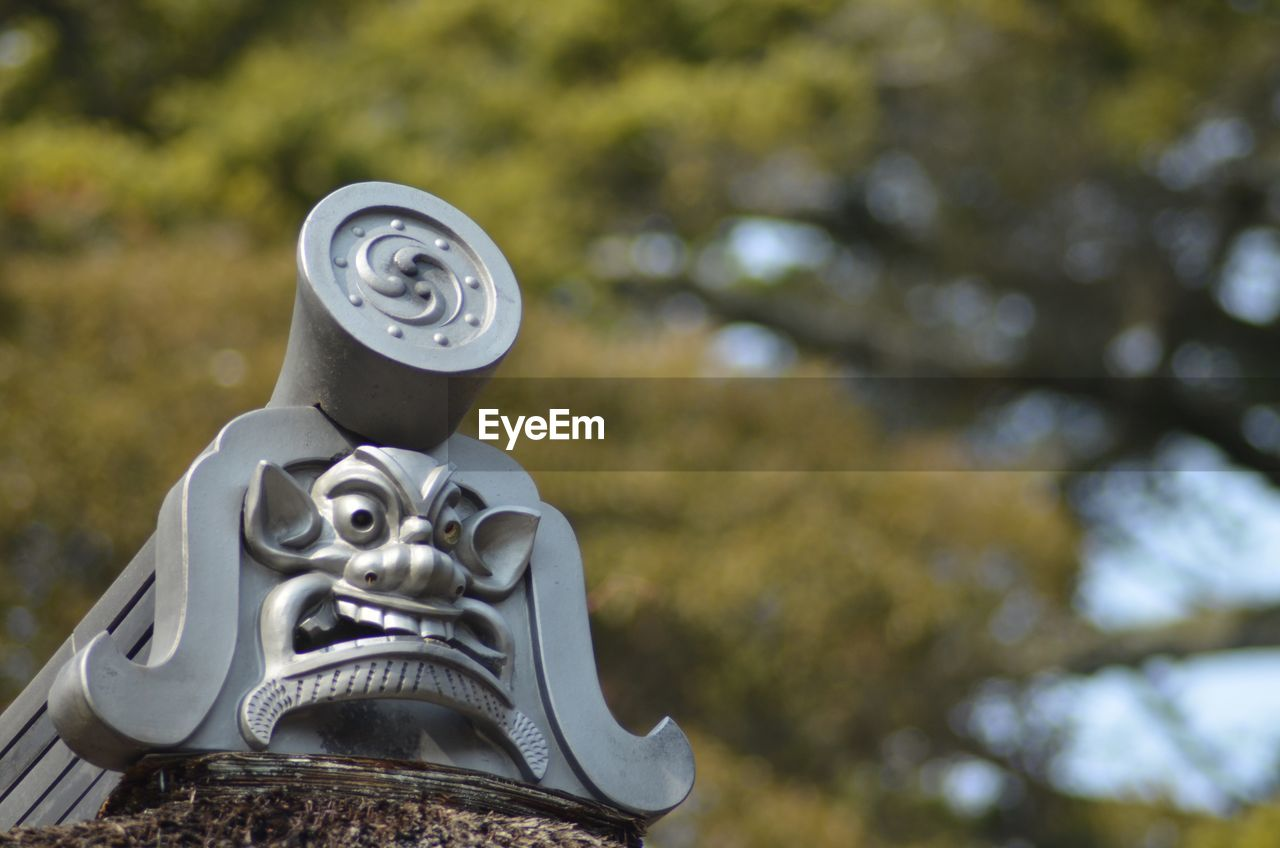 focus on foreground, low angle view, no people, outdoors, day, sculpture, statue, close-up, tree, sky