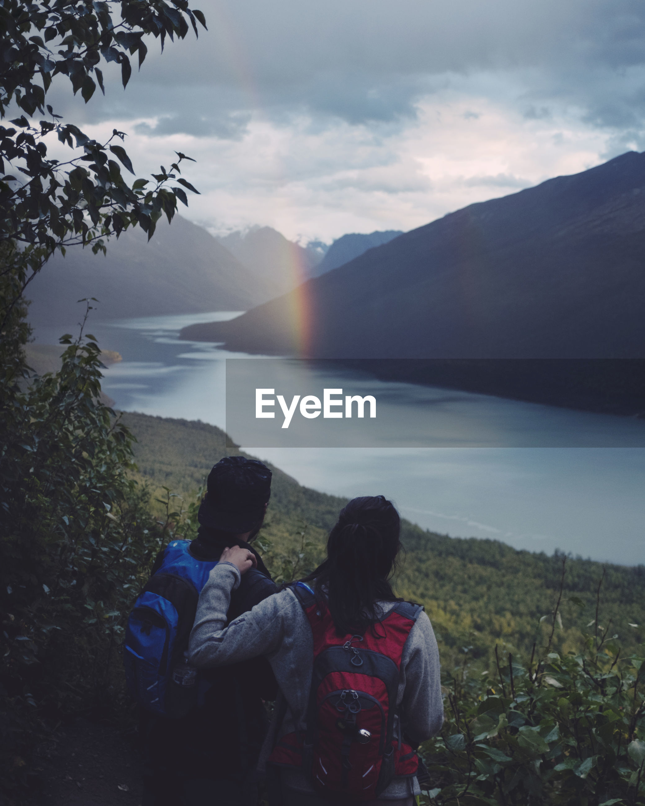 Friends looking at lake and mountains during sunset