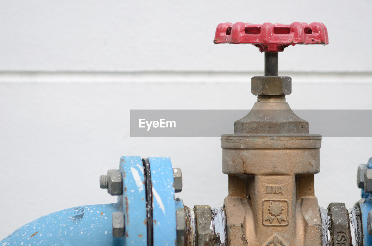 Close-up of valve against white wall