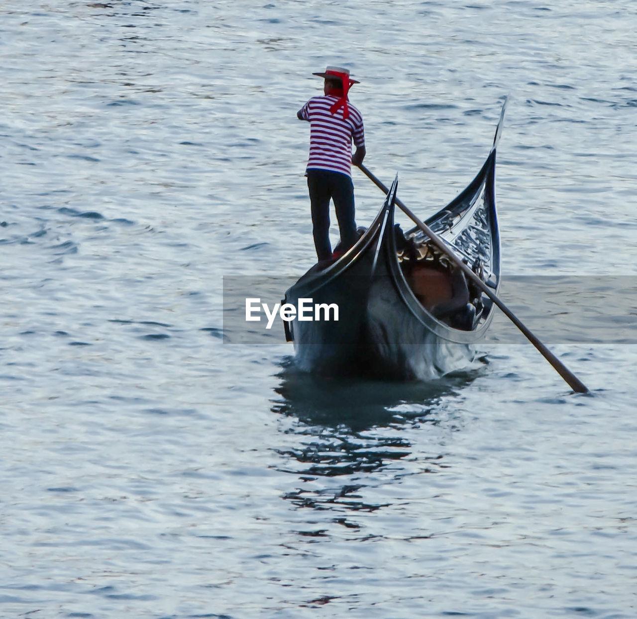 Gondolier Sailing On Gondola Over Grand Canal