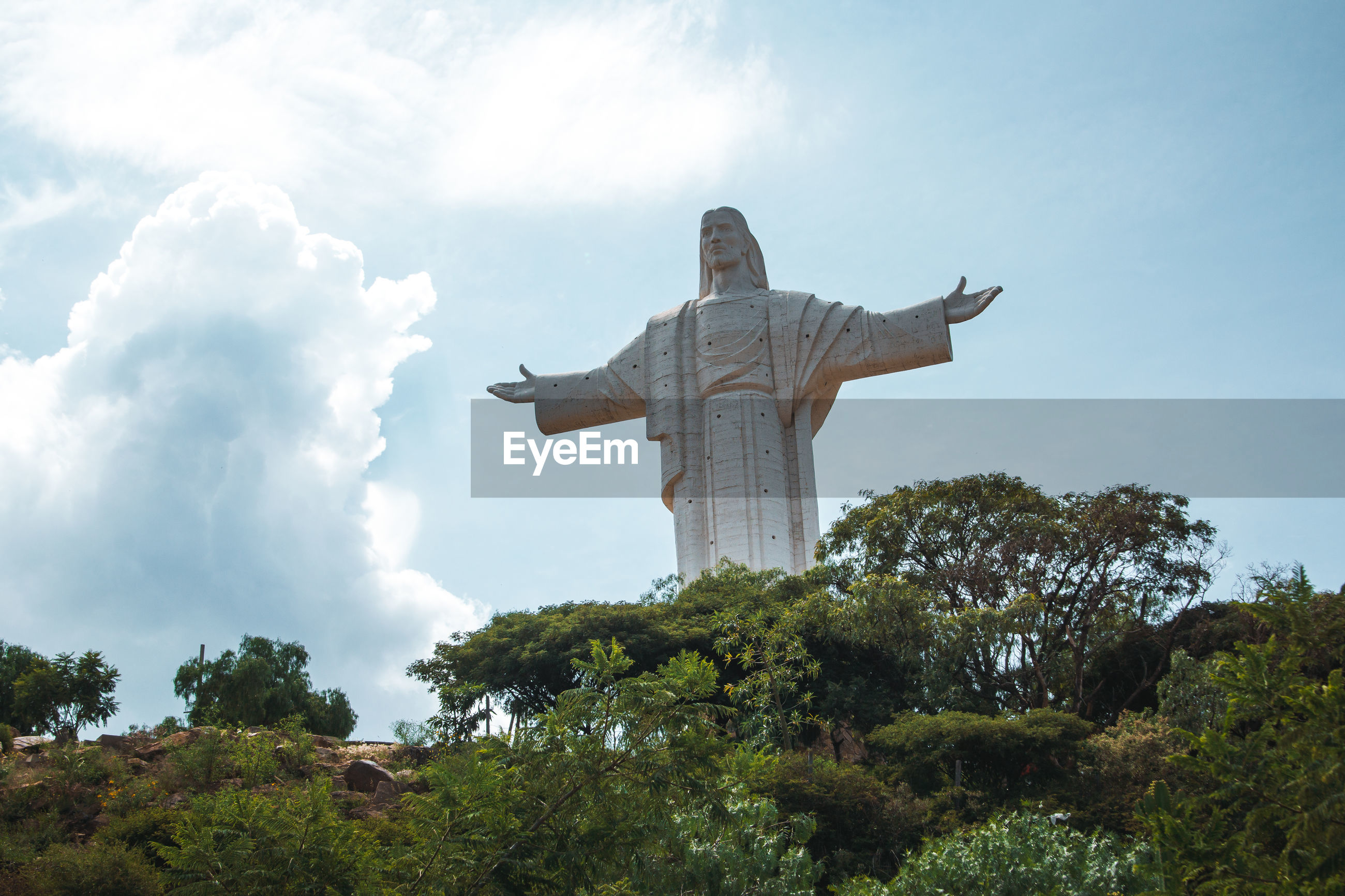 Low angle view of jesus statue against sky