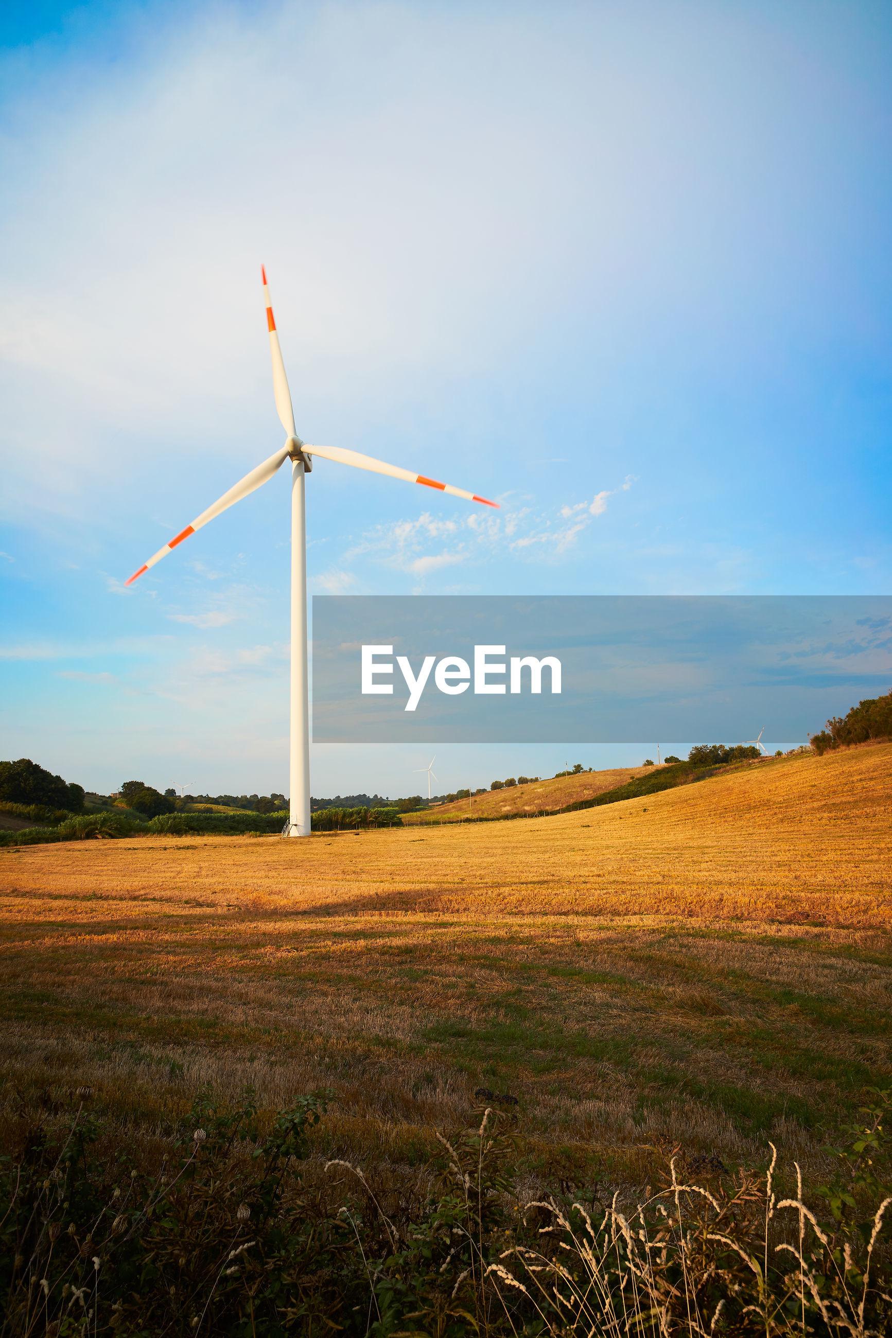 A wind turbine in field between hills in italy