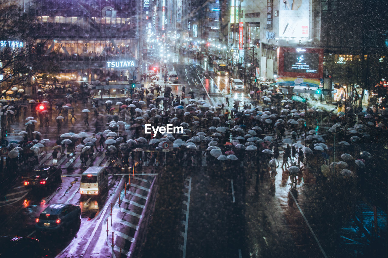 architecture, city, illuminated, night, building exterior, built structure, street, city life, wet, transportation, rain, crowd, group of people, city street, water, large group of people, travel destinations, mode of transportation, high angle view, outdoors