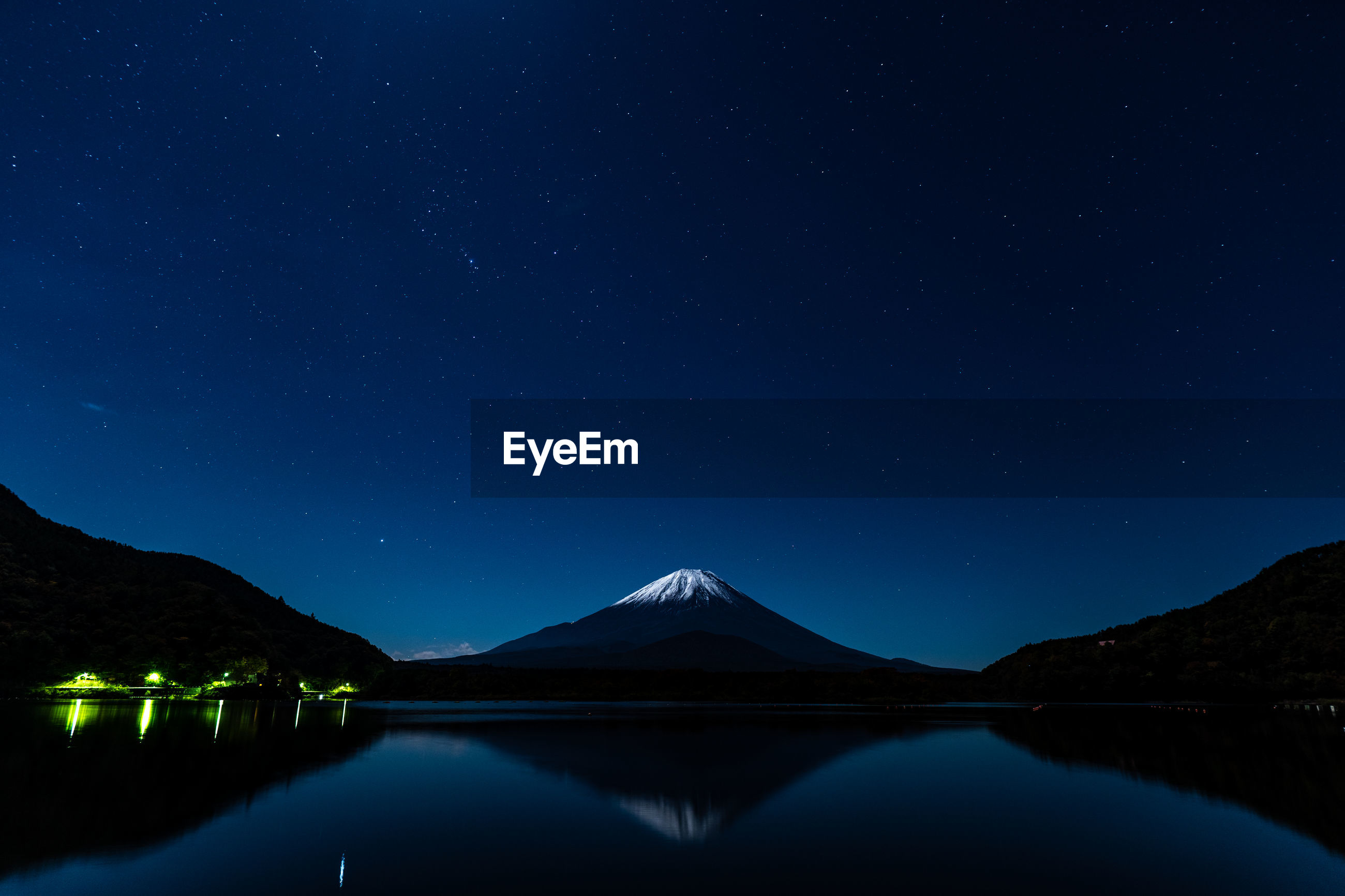 Scenic view of lake and snowcapped volcano against sky at night