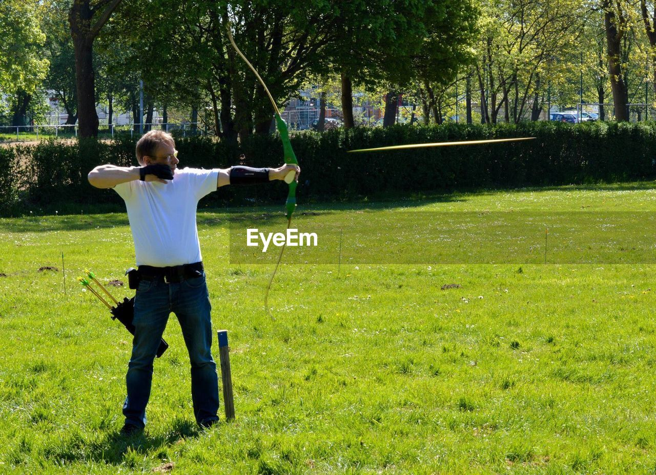Full Length Of Man Shooting Arrow On Grassy Field During Sunny Day