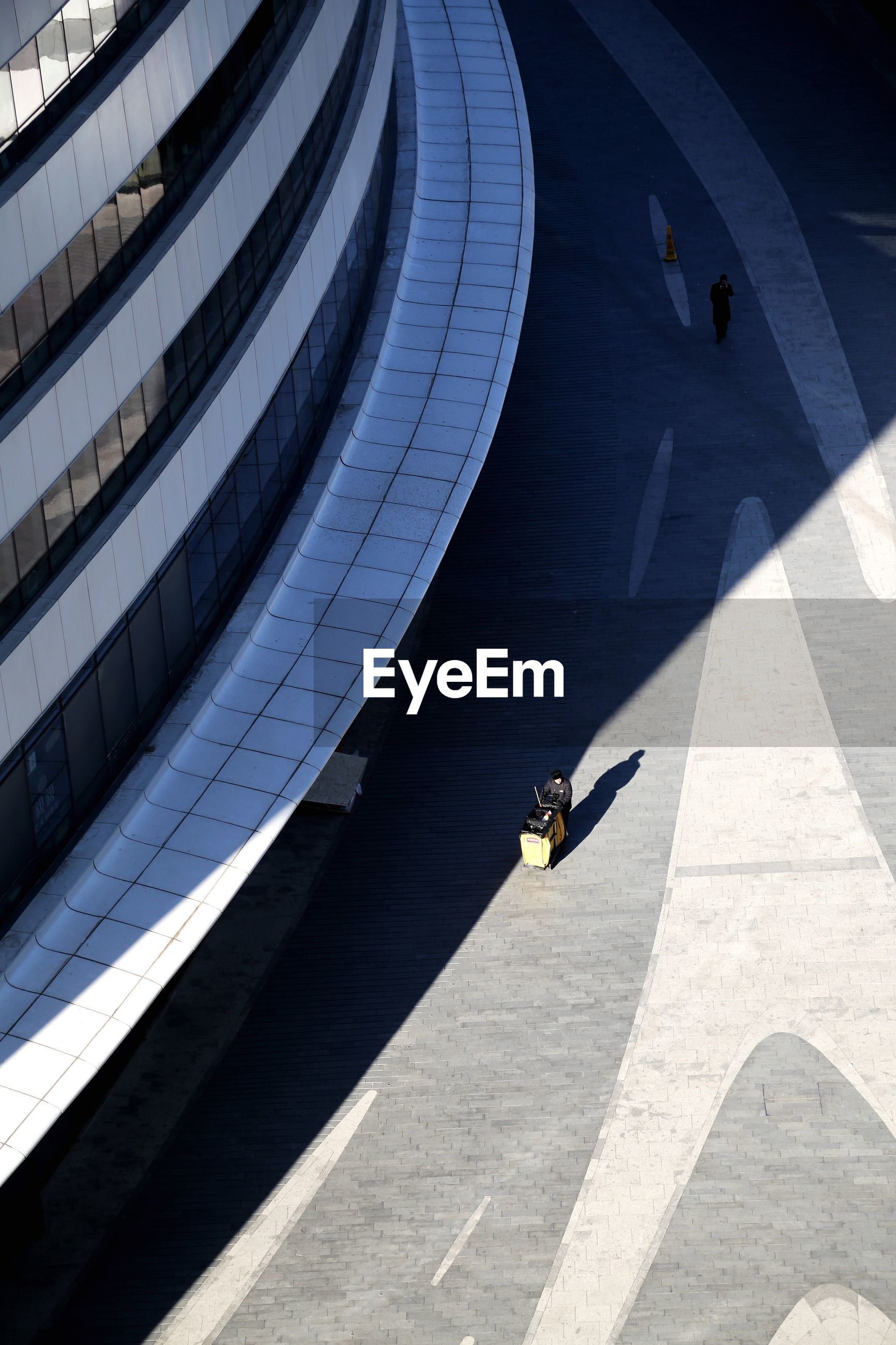 High angle view of person walking on footpath outside office building