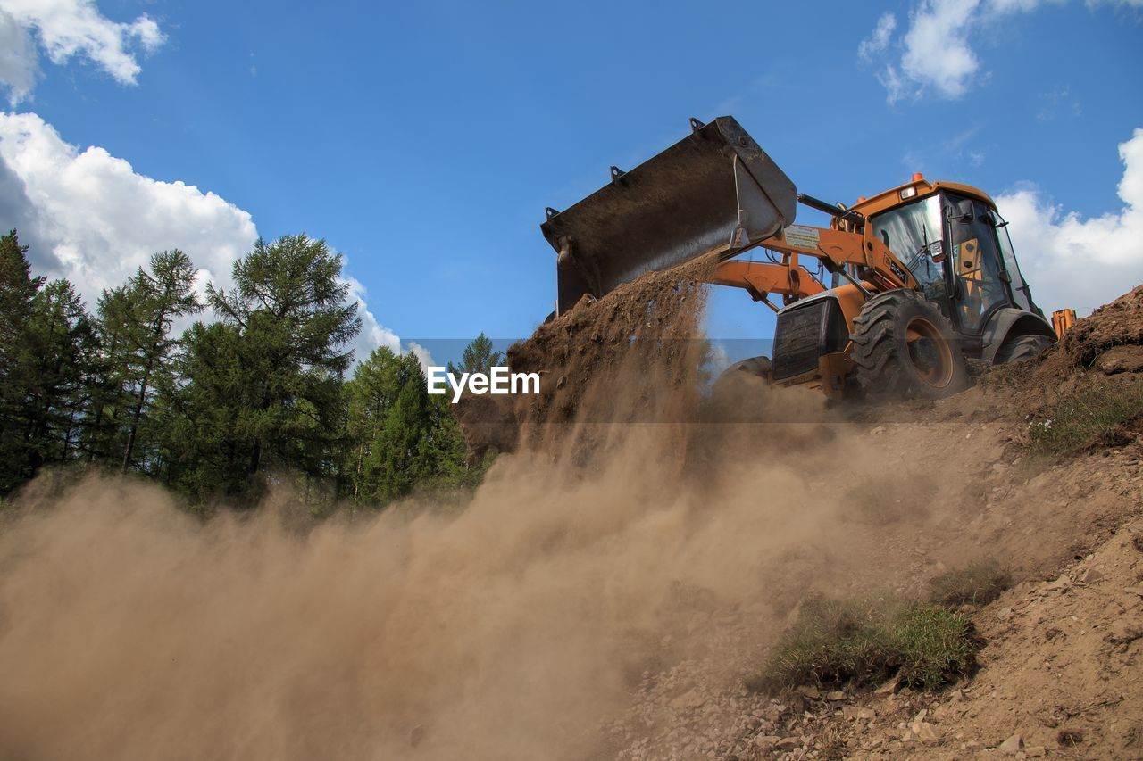sky, machinery, transportation, nature, mode of transportation, land, land vehicle, day, cloud - sky, plant, construction industry, motion, field, landscape, construction machinery, outdoors, low angle view, tree, dust, earth mover, quarry, construction equipment