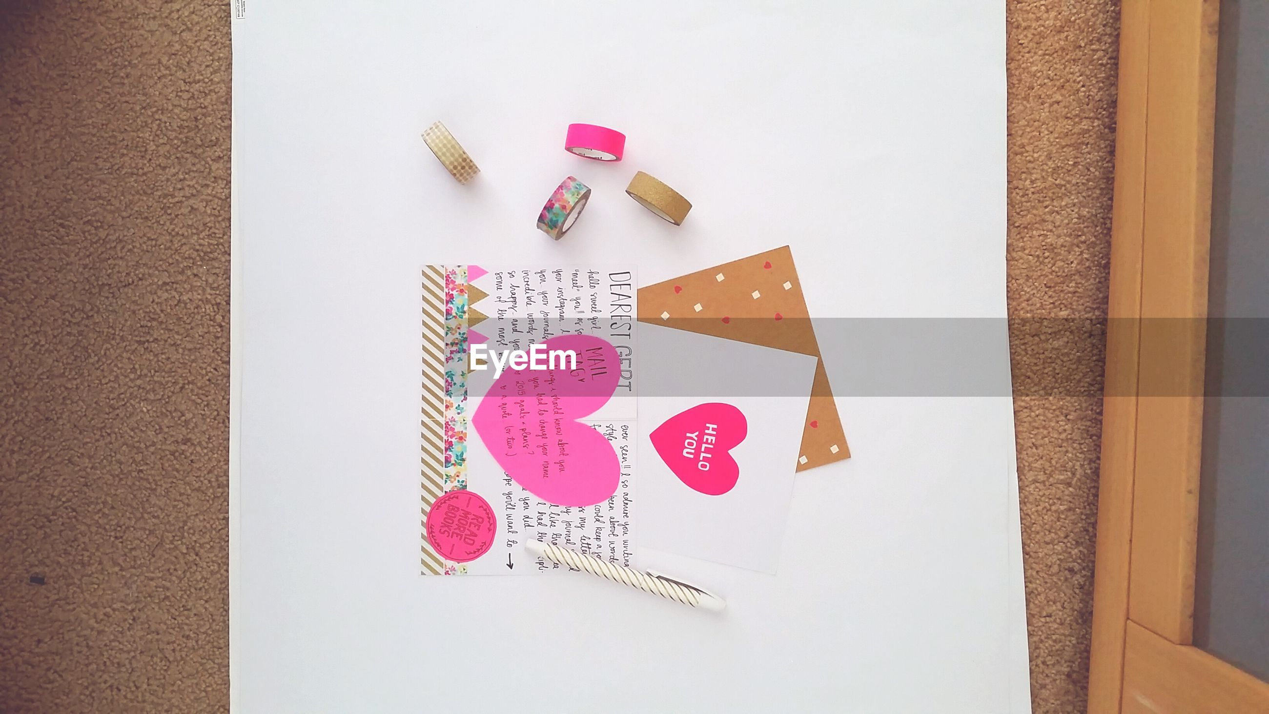 indoors, text, western script, communication, creativity, still life, art, table, paper, art and craft, wall - building feature, heart shape, love, close-up, human representation, red, high angle view, no people, decoration, animal representation