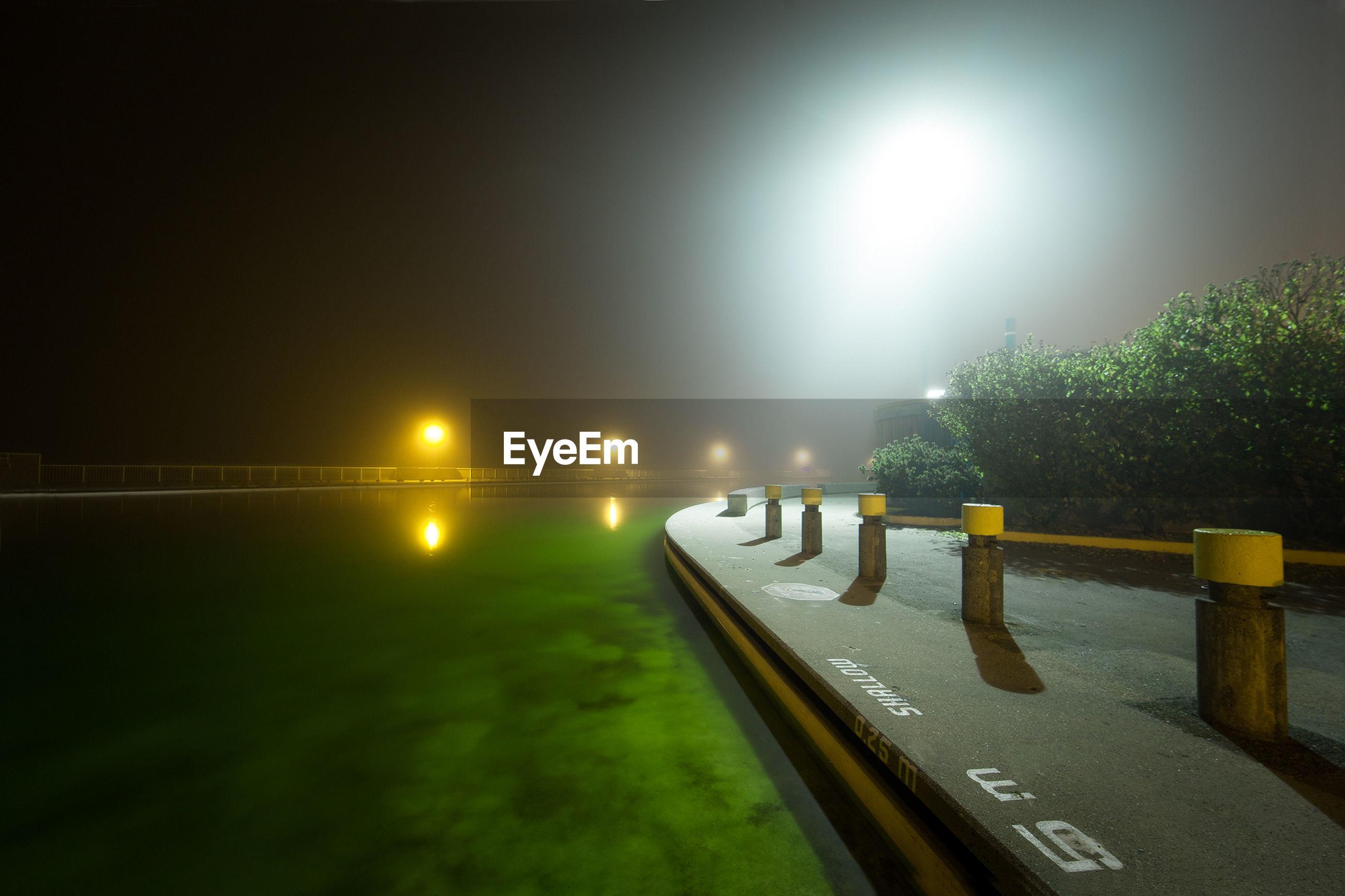 ILLUMINATED STREET AGAINST SKY AT NIGHT