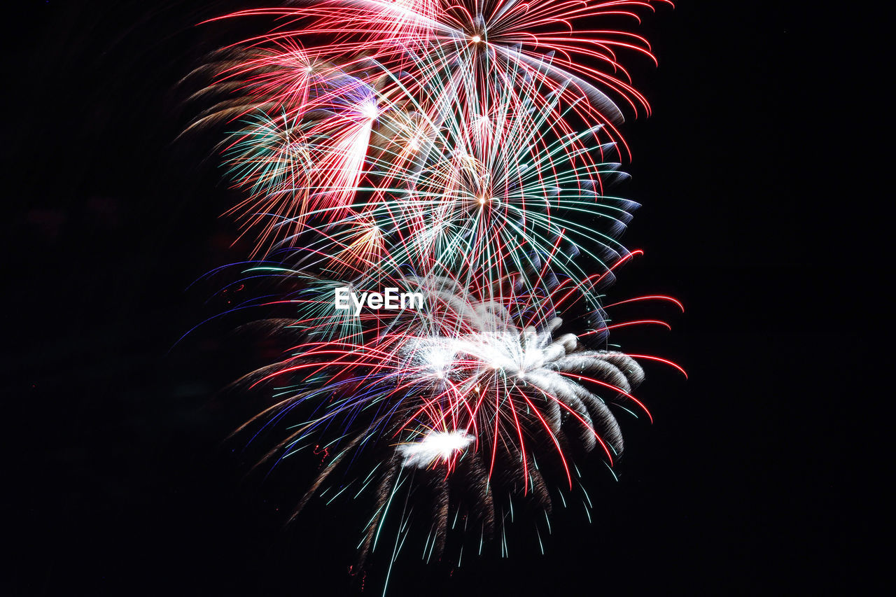 firework display, celebration, firework - man made object, exploding, night, long exposure, sparks, event, arts culture and entertainment, multi colored, motion, low angle view, illuminated, glowing, blurred motion, smoke - physical structure, firework, no people, sky, black background, outdoors