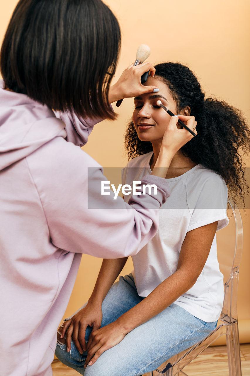 Woman applying eyeliner to female