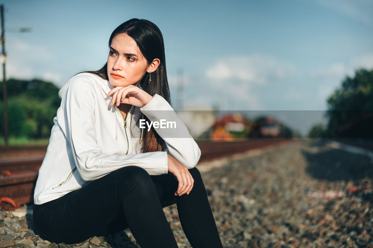Thoughtful Young Woman Sitting On Railroad Track