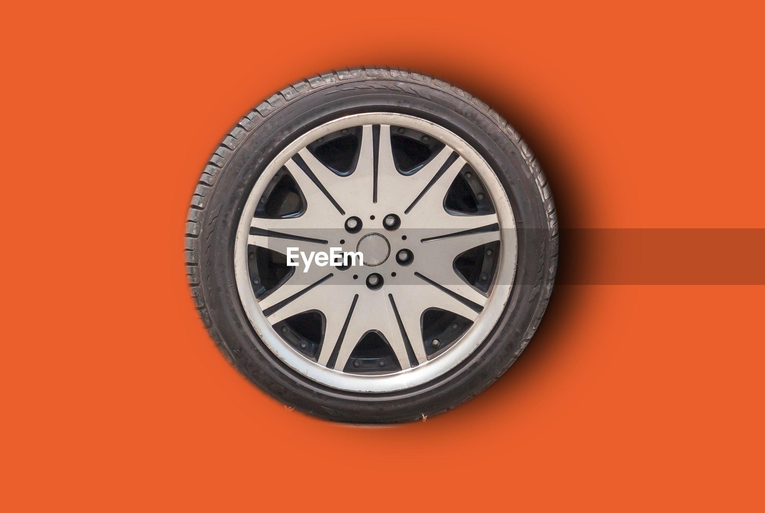 Close-up of wheel against orange background