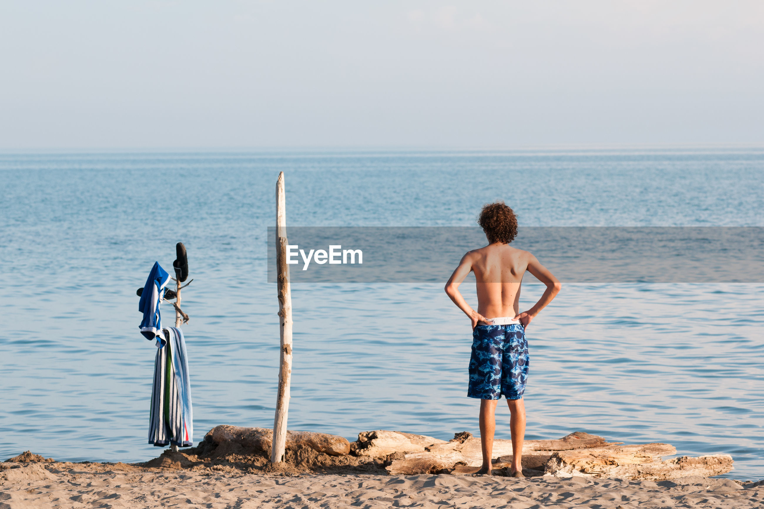 Rear view of shirtless teenage boy with hand on hip standing at beach against sky