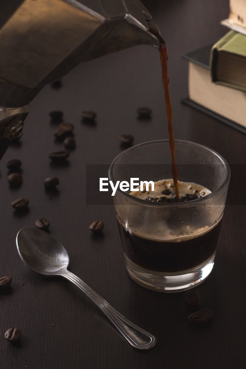Espresso being poured in cup on table
