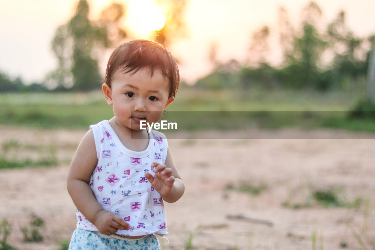 Portrait of cute baby girl standing on land