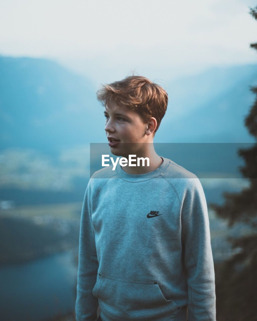 BOY STANDING AGAINST MOUNTAIN