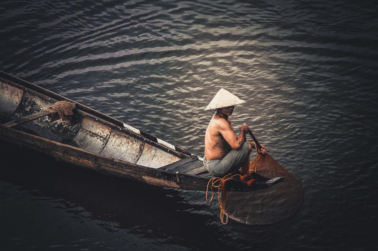 Shirtless Man Sailing Boat On Lake