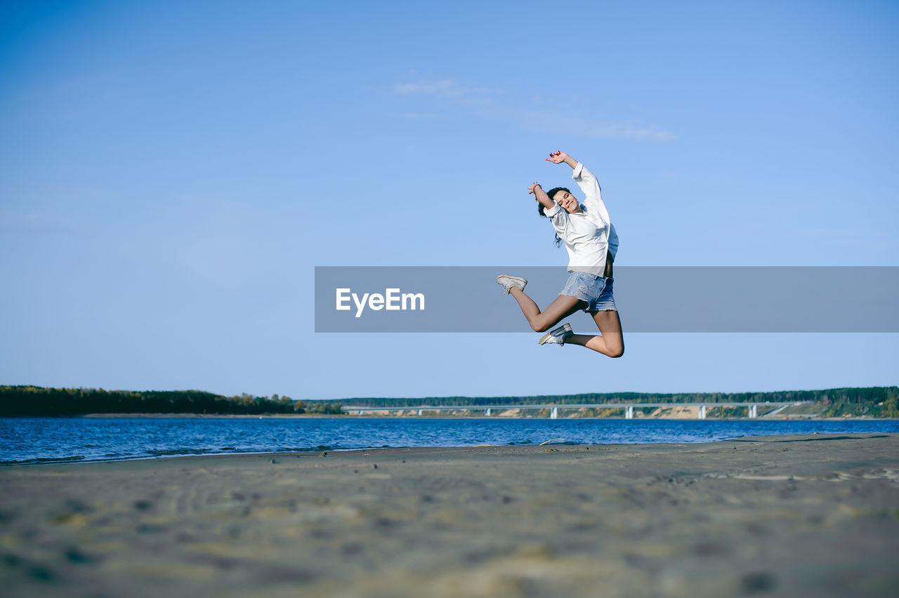 Woman Jumping At Beach Against Blue Sky