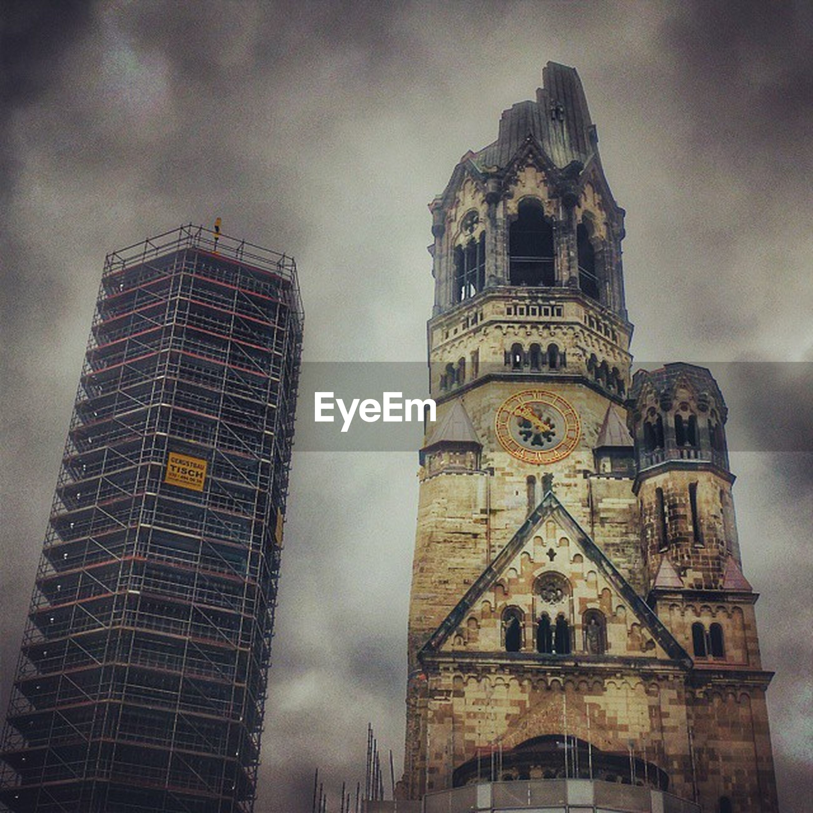 architecture, building exterior, built structure, low angle view, sky, tower, cloud - sky, cloudy, tall - high, religion, church, place of worship, clock tower, travel destinations, city, cloud, famous place, outdoors, spirituality