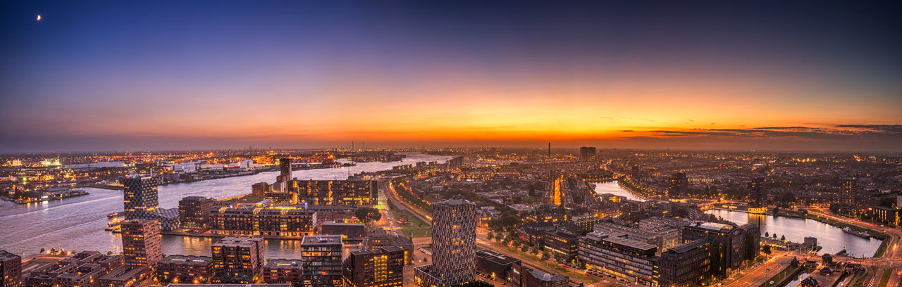 High Angle View Of City Lit Up At Sunset