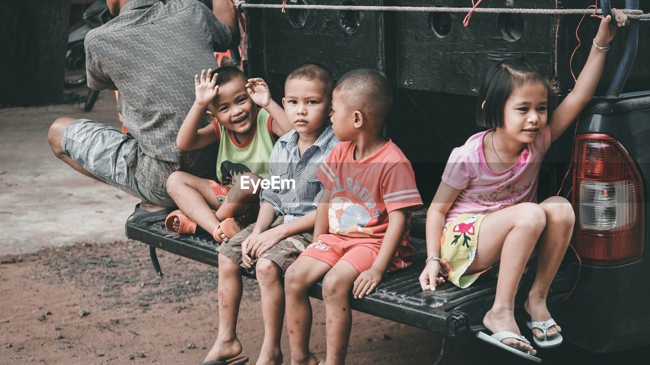 childhood, child, sitting, real people, girls, leisure activity, men, women, boys, full length, group of people, males, casual clothing, people, innocence, lifestyles, togetherness, front view, positive emotion, sister, outdoors