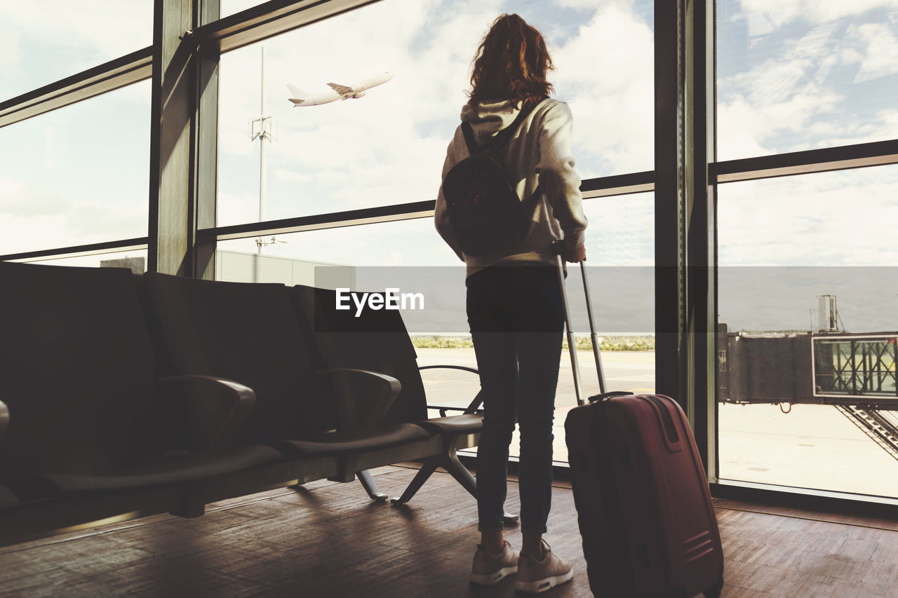 Rear view of girl with luggage standing in waiting room