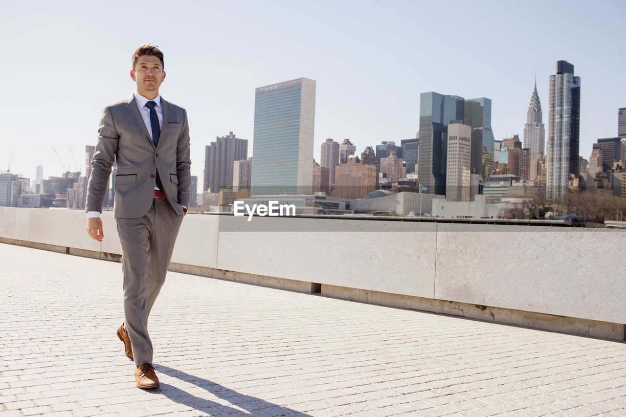 FULL LENGTH OF MAN BY BUILDINGS AGAINST SKY IN CITY IN BACKGROUND