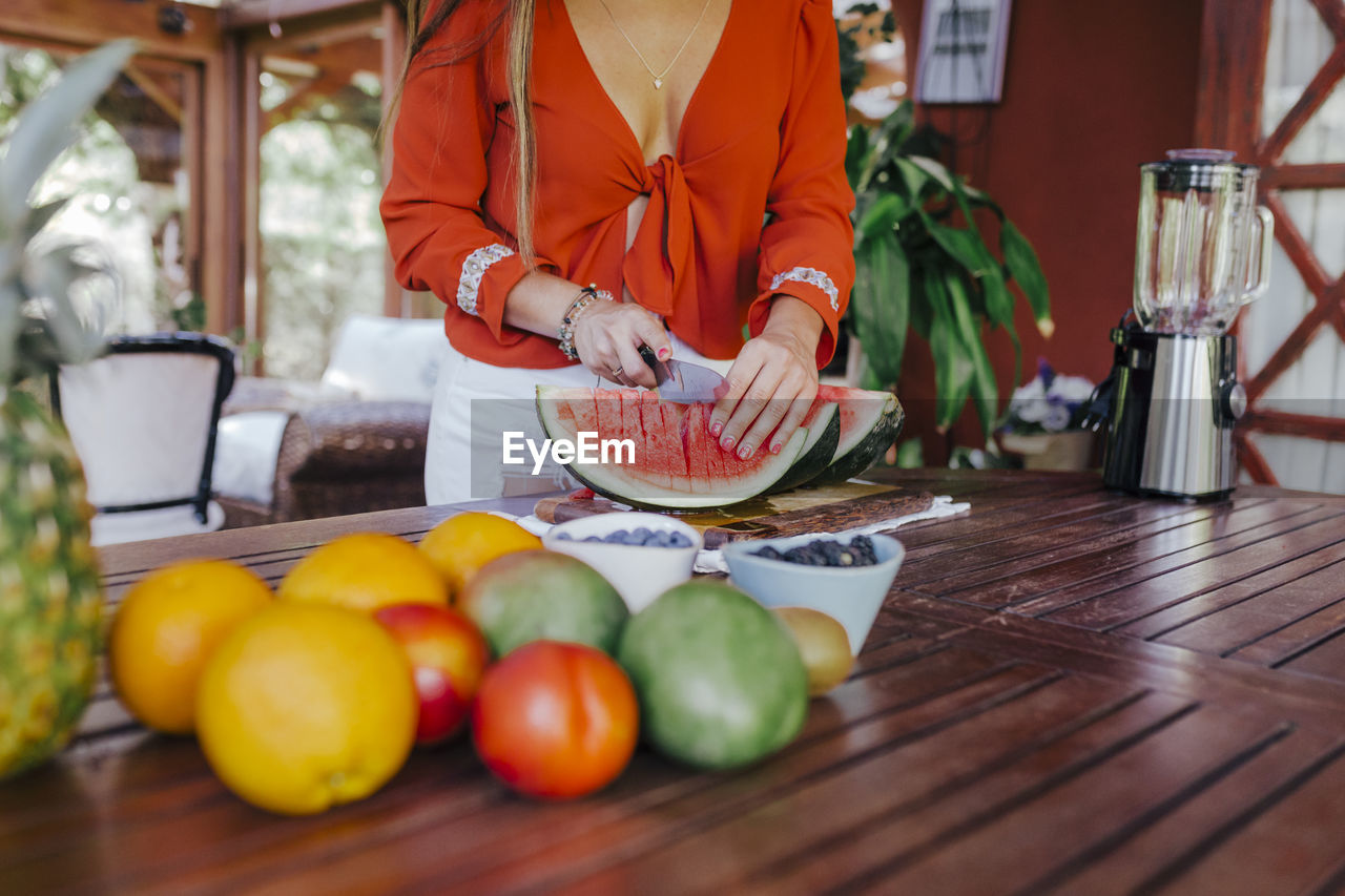 food, food and drink, one person, freshness, healthy eating, midsection, real people, wellbeing, fruit, table, indoors, preparation, standing, vegetable, holding, tomato, day, lifestyles, adult, preparing food, orange