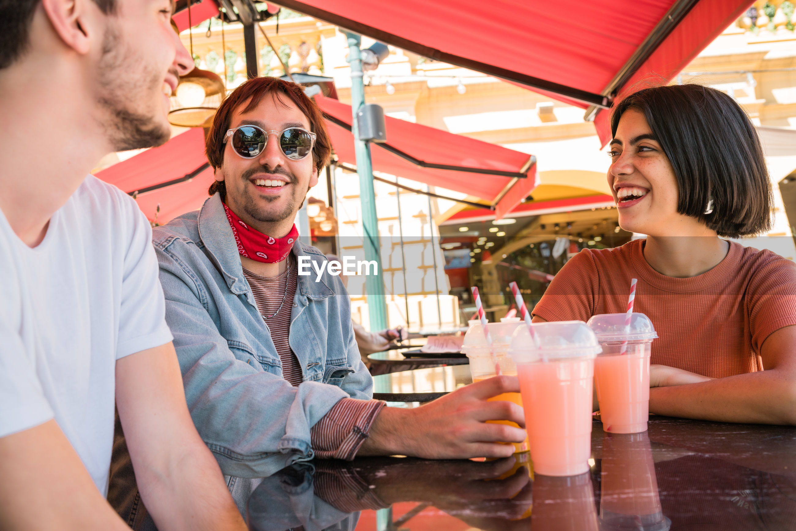 Smiling friends having discussion sitting at cafe