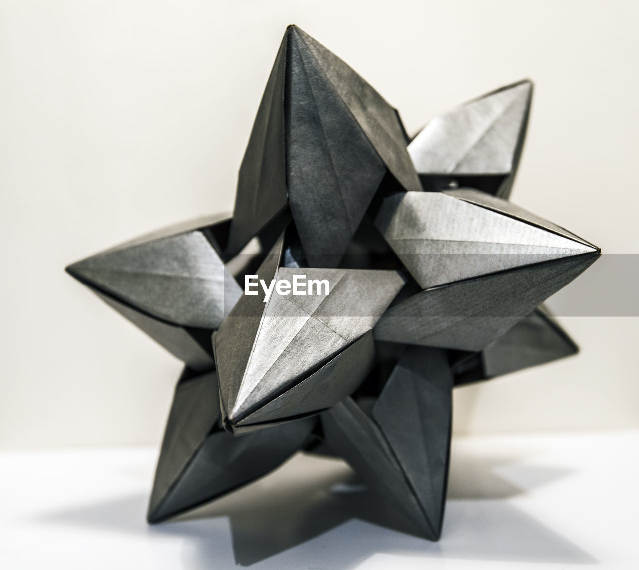 close-up, still life, origami, no people, indoors, creativity, art and craft, focus on foreground, shape, studio shot, paper, craft, white background, representation, design, star shape, toy, table, large group of objects, metal, silver colored