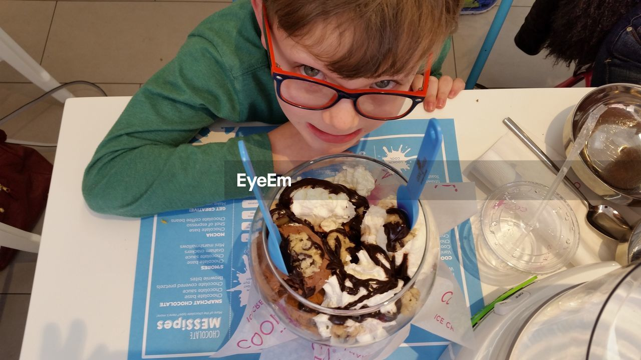 real people, one person, indoors, sweet food, food and drink, dessert, childhood, food, ice cream, table, lifestyles, freshness, indulgence, leisure activity, holding, boys, frozen food, ready-to-eat, close-up, day, ice cream sundae