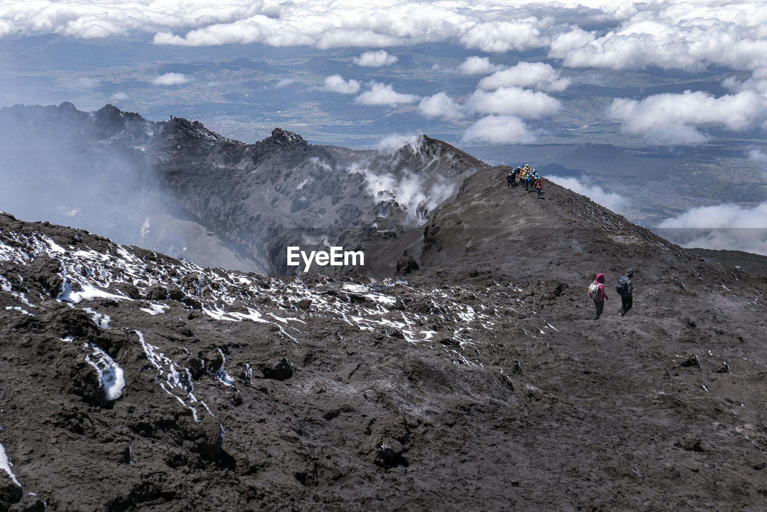 MEN WALKING ON MOUNTAIN AGAINST SKY
