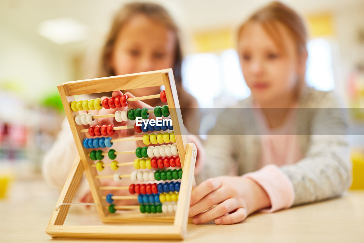 Friends playing with abacus in classroom