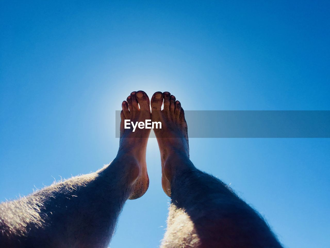 Low Section Of Male Feet Against Blue Sky