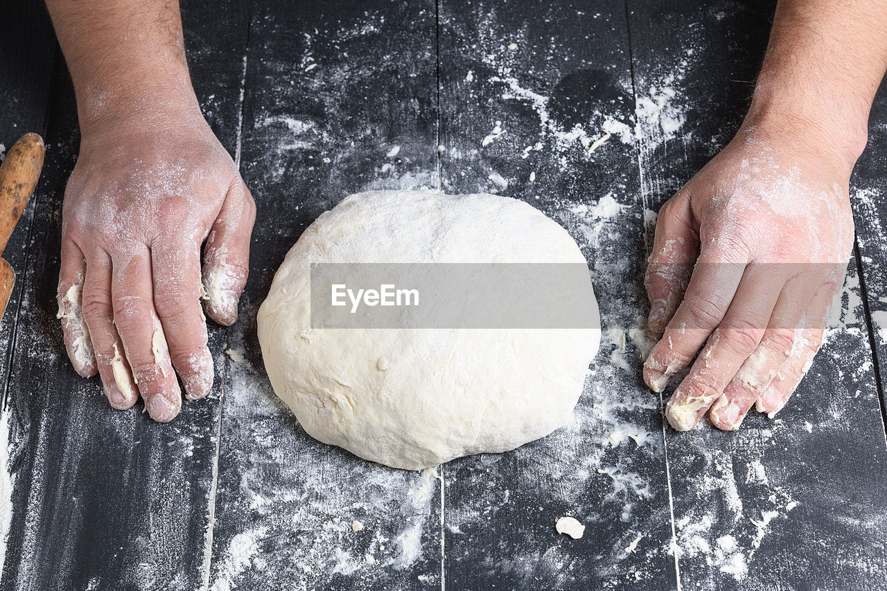 Cropped hands of person by dough on table