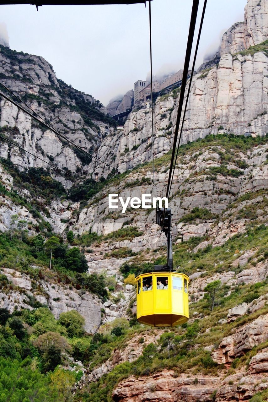 Low angle view of overhead cable car against rocks