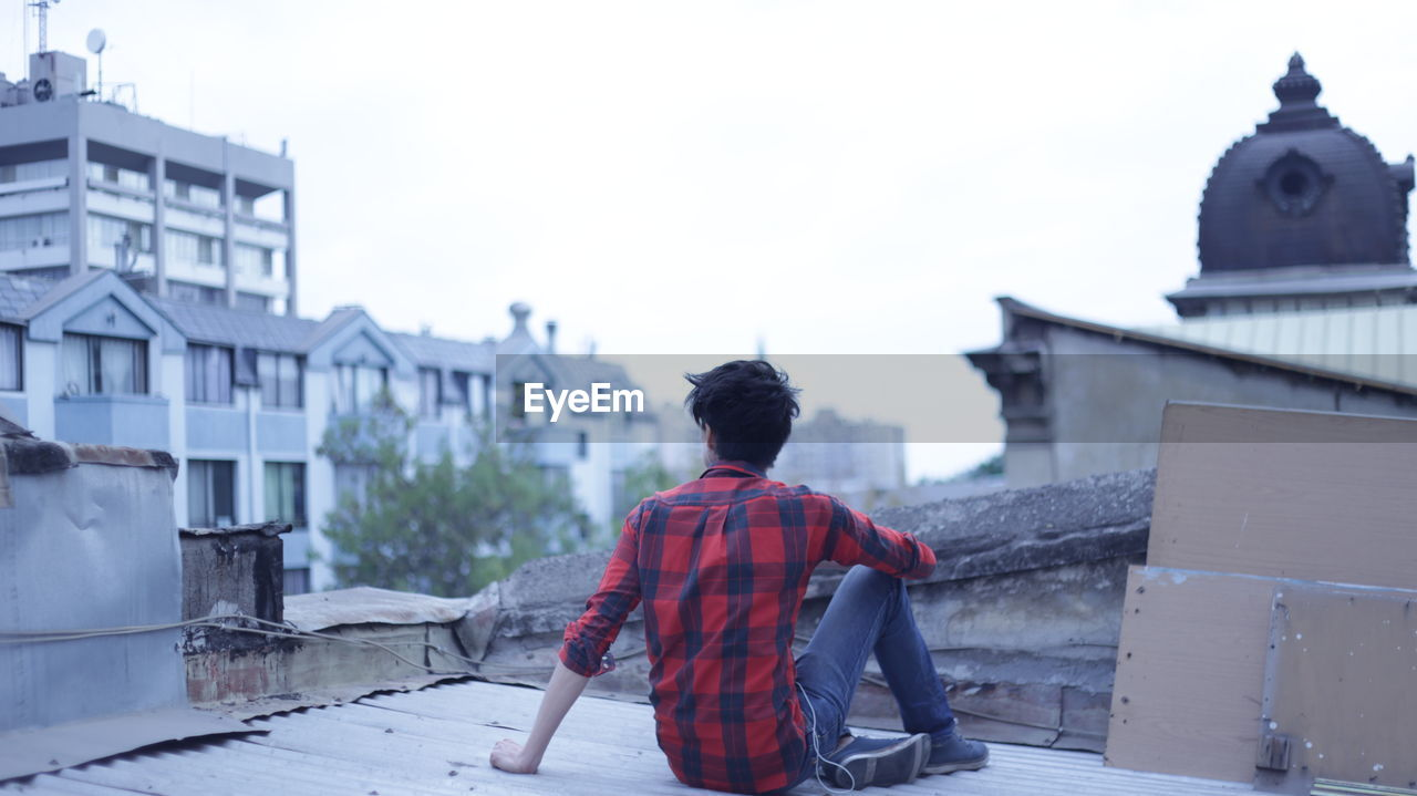 Rear view of man sitting on building terrace against clear sky