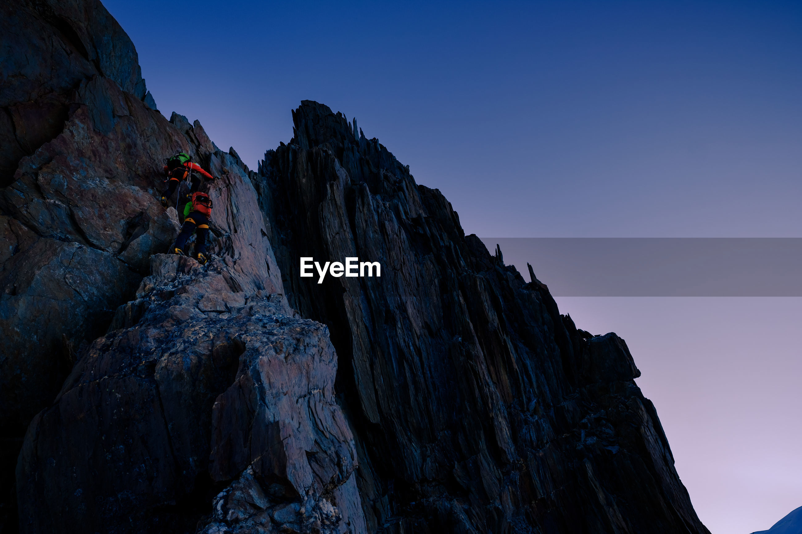 Low angle view of people climbing rocky mountain against sky during sunrise
