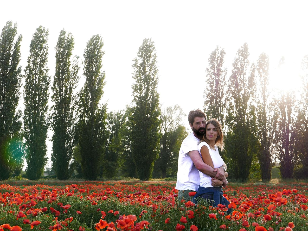 Couple standing amidst poppies on field