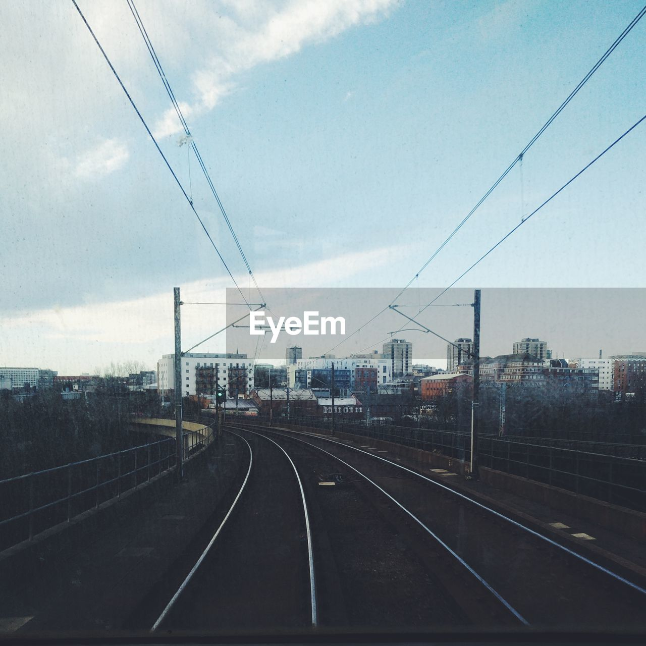 cable, transportation, power line, railroad track, sky, connection, power supply, rail transportation, electricity pylon, day, electricity, no people, the way forward, windshield, mode of transport, public transportation, outdoors, nature, built structure, technology, architecture